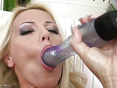 Blonde milf wearing only a couple of hot black nylons is playing solo with her large dildo, that sweetheart sucks it and the fills her shaved wet crack with it, fucking herself as hard as that sweetheart can but that is not enough. Luckily her dark brown girlfriend is ready to aid and gives her a hand, rubbing her muff and then fingering it, want to watch what else she's ready to do?